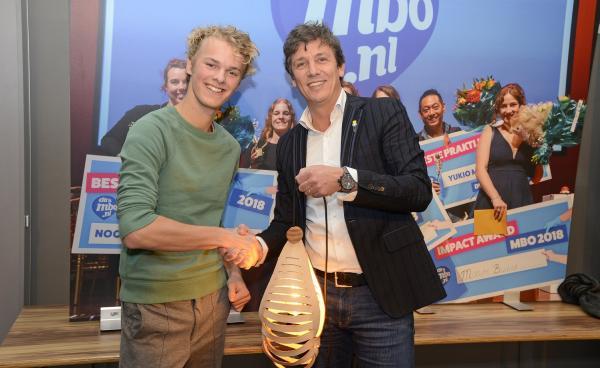 Cibap-student Karel Haans reikt aan de voorzitter van MKB-Nederland zijn zelfgemaakte lamp uit.